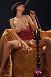 Busty glamour brunette in red lingerie is smoking hookah