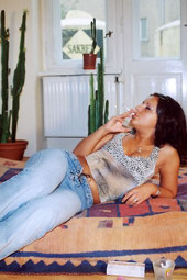 Brunette is smoking at home dressed in tight blue jeans