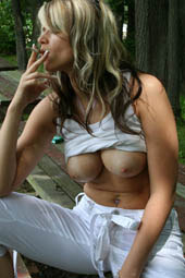 Beautiful sexy blonde is flashing and smoking on the bench outdoor
