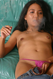 Asian chick wearing a tight blue jeans is smoking a brown cigarette having her nipples erected