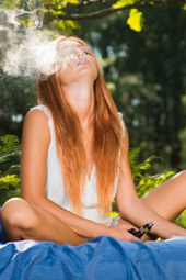 Exciting sexy redhead beauty is smoking at the forest nude picnic