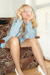 Sexy blonde smoker wearing jeans suit and high heels
